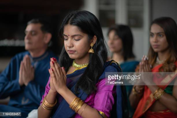 a beautiful indian family sits in their living room one afternoon praying together. they are celebrating and giving thanks during the holiday diwali. they are bonding as they are donned in traditional clothing. - hinduism stock pictures, royalty-free photos & images