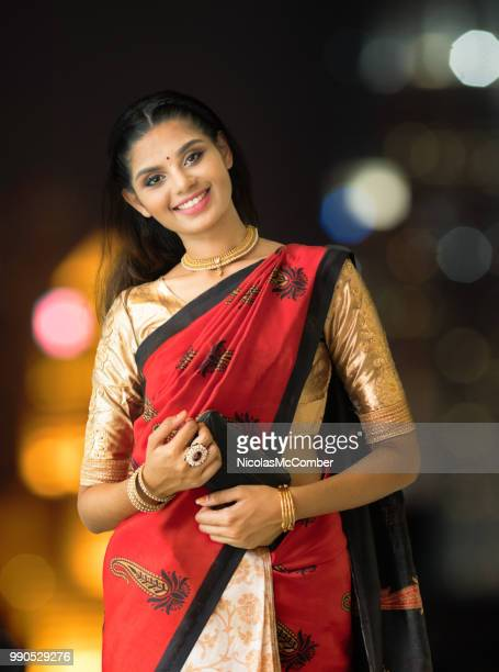 beautiful indian female portrait in red and gold dress night urban background - sari stock pictures, royalty-free photos & images