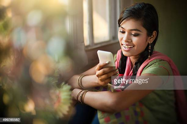 beautiful indian girl reading sms at the time of festival. - girls stock pictures, royalty-free photos & images