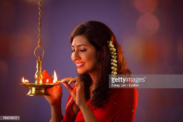 beautiful indian woman in red sari lighting diya during diwali - diwali celebration stock photos and pictures