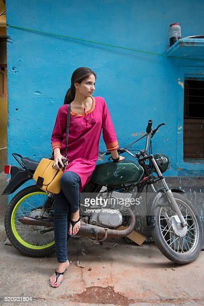 Beautiful Indian woman standing next to her motorbike.