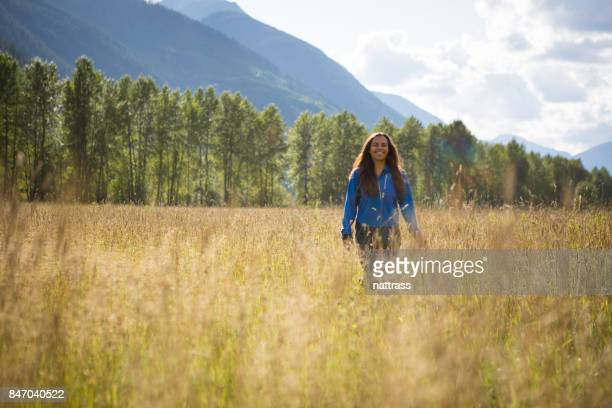 Beautiful Indigenous Canadian woman walks through a field