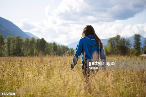Beautiful indigenous Canadian woman wondering through a field