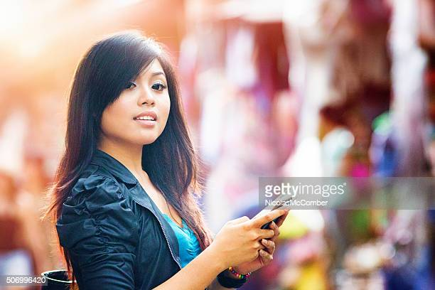 Beautiful Indonesian woman interrupts her text messaging