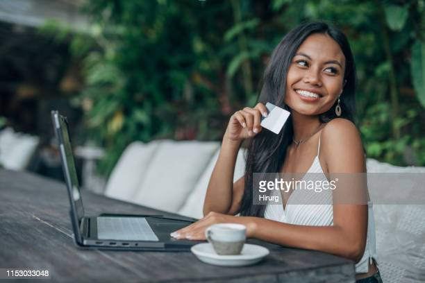 beautiful indonesian woman using credit card - indonesian culture stock pictures, royalty-free photos & images