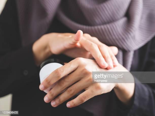 beautiful islamic woman applying hand cream - handcrème stockfoto's en -beelden