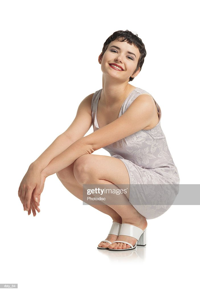 beautiful italian looking young woman with short dark hair beautiful features and red lips wearing a short purple dress and white shoes squats down with arms outstretched in front of her tilts her head and smiles at the camera : Foto de stock