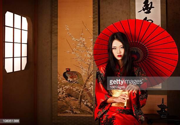Wunderschönen japanischen geisha mit einem roten Regenschirm