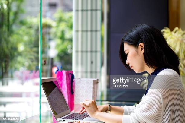 Beautiful Japanese Girl working her laptop while waiting for her friend