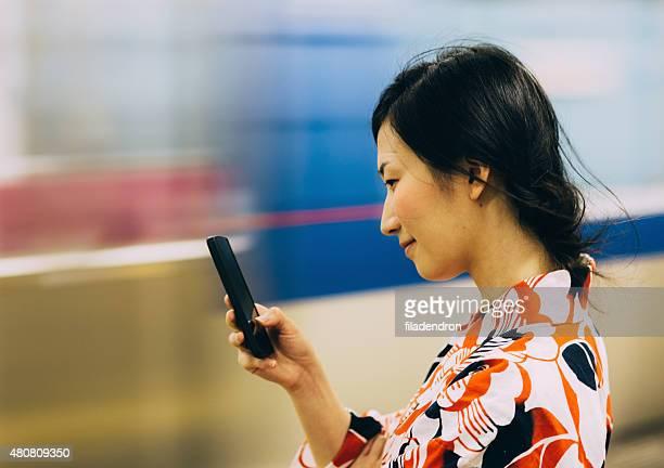 Belle femme japonaise envoyer des SMS sur le téléphone