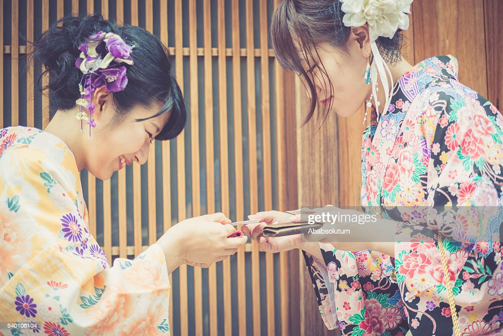 Beautiful japanese women in kimono exchanging business cards kyoto beautiful japanese women in kimono exchanging business cards kyoto japan stock photo reheart Image collections