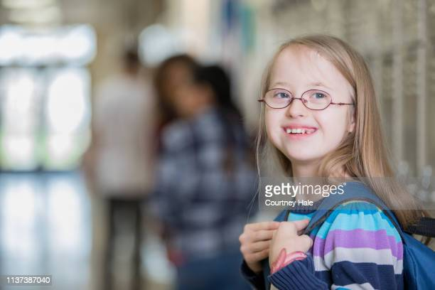 beautiful junior high school student with down syndrome smiles on her way to class - learning disability stock pictures, royalty-free photos & images