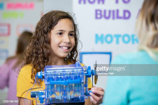 beautiful junior high student with curly hair holds motor she built for a science fair - junior girl models stock pictures, royalty-free photos & images