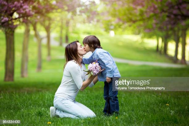 beautiful kid and mom in spring park, flower and present. mothers day celebration concept - little girls giving head stock photos and pictures