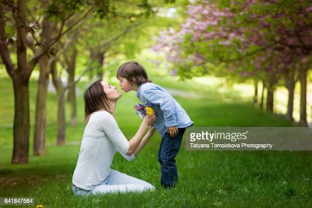 beautiful kid and mom in spring park, flower and present - little girls giving head stock photos and pictures