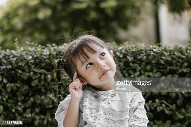 schönes kind spielt thinker mit ernster - antworten stock-fotos und bilder