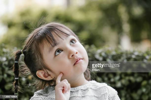 beautiful kid playing thinker with serious - domanda e risposta foto e immagini stock