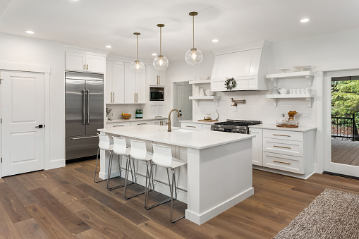 beautiful kitchen in new luxury home with island, pendant lights, and hardwood floors 1054756164
