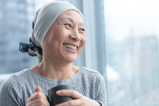 Beautiful Korean woman with cancer looks out window 1141776218