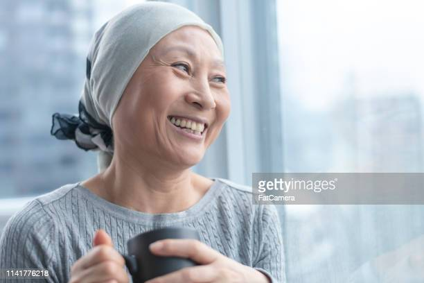beautiful korean woman with cancer looks out window - cancer stock photos and pictures