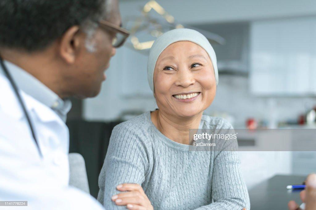 Mooie Koreaanse vrouw met kanker glimlacht bij Doctor : Stockfoto