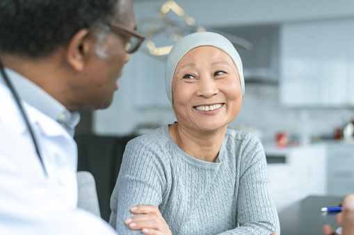 Beautiful Korean woman with cancer smiles at doctor 1141776224
