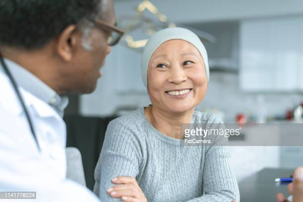 beautiful korean woman with cancer smiles at doctor - cancer stock photos and pictures