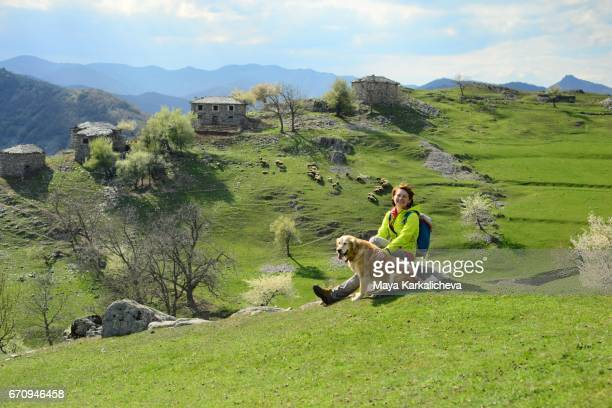 Beautiful lady and her dog near a small village in Rhodope