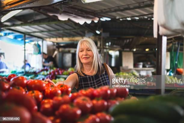 beautiful lady choosing tomatoes - bancarella di verdura foto e immagini stock