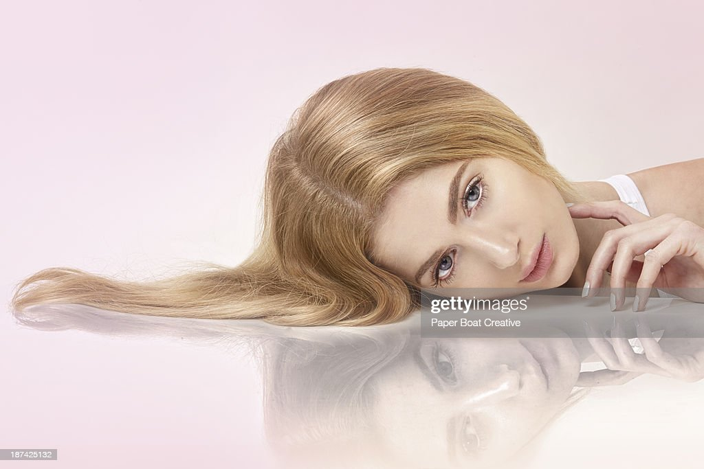 Beautiful lady lying on a mirror with hair spread : Stock Photo
