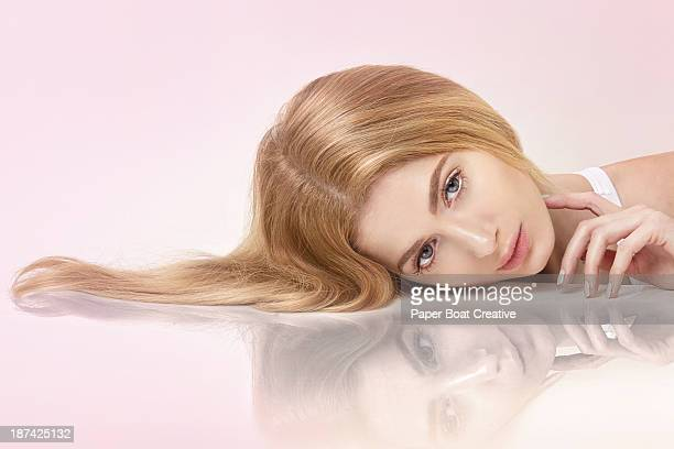 Beautiful lady lying on a mirror with hair spread