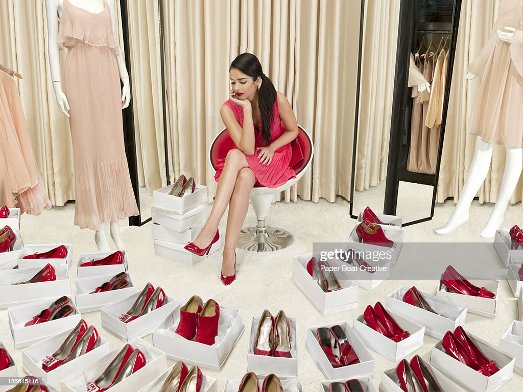 beautiful lady trying on a pair of new red shoes : Stockfoto