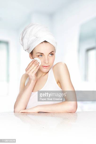 Beautiful lady wiping her cheek with a cotton pad