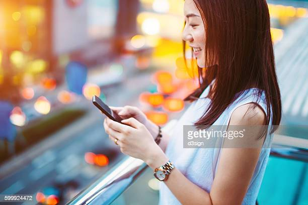 Beautiful lady with toothy smile text messaging on smartphone in busy city street.