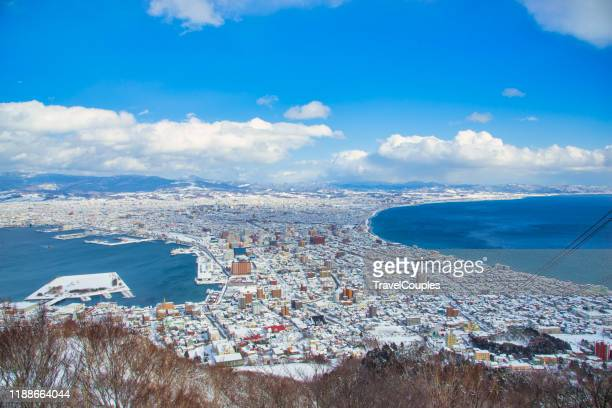 beautiful landscape and cityscape from mountain hakodate for look around city skyline building and architecture with blue sky white cloud. hakodate, hokkaido, japan city skyline from mt. hakodate at dusk in autumn season. - hokkaido stock pictures, royalty-free photos & images