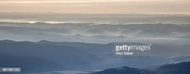 Beautiful landscape mountain with far way view composed with all mountains in different layers in nice blue colors during foggy sunrise in the Catalan Pyrenees.