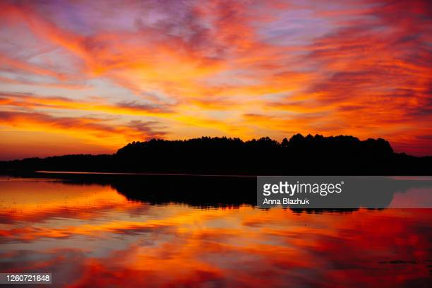 beautiful landscape of lake in the sunrise, horizon. dramatic sky, vibrant clouds and sunlight reflection on the calm water. serene scenery. - anna fischer stock-fotos und bilder