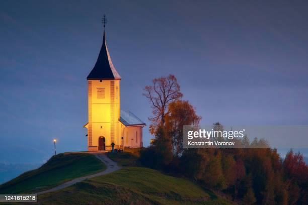 beautiful landscape of the church of st primoz in jamnik, slovenia. famous viewpoint, travel destination. night illumination of the building. - kranj fotografías e imágenes de stock