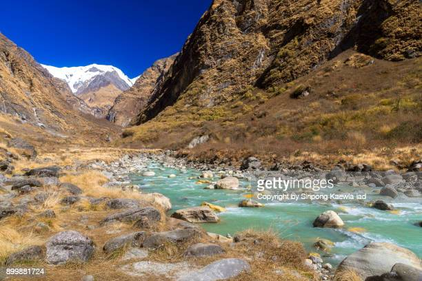 Beautiful landscape of the massif, valley, grassland and the turquoise colored river during the way to Annapurna Base Camp (ABC).