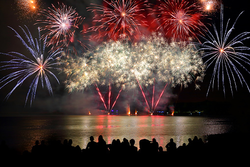Beautiful large colorful fireworks display with unrecognizable crowd people watching 599997926