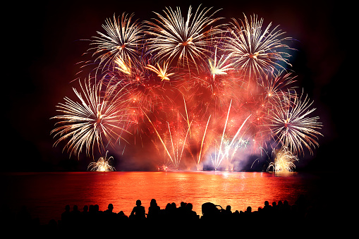 Beautiful large colorful fireworks display with unrecognizable crowd people watching 599999562