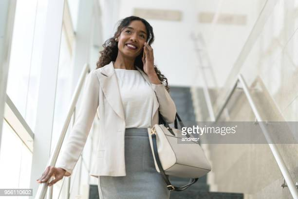 beautiful latin american black business woman talking on the phone while walking down the stairs - black purse stock pictures, royalty-free photos & images