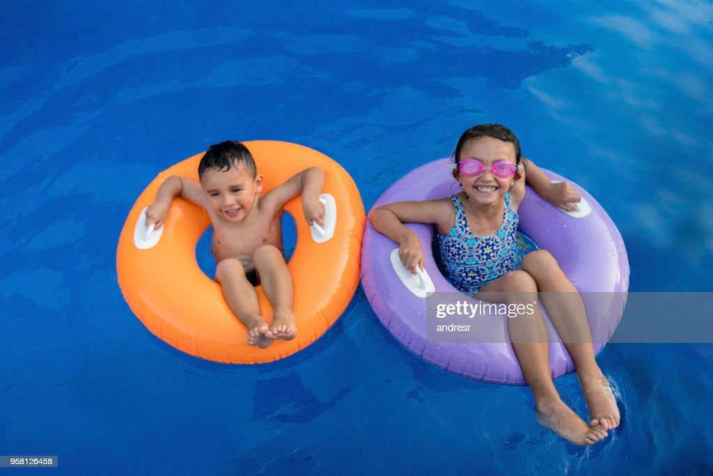 Beautiful Latin American Brother And Sister On Inflatable Tubes Looking At Camera With Excitement Stock