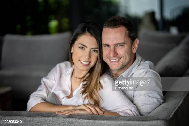Beautiful latin american couple at home sitting on the couch embracing each other looking at camera smiling