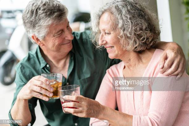 beautiful latin american elder couple hugging while toasting at a bakery - hispanolistic stock photos and pictures