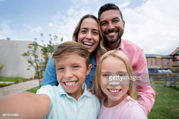 beautiful latin american family at the park and little boy taking a selfie all looking at camera with a toothy smile - beautiful wife pics stock pictures, royalty-free photos & images