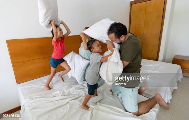 Beautiful latin american family having a pillow fight in hotel room and kids having a great time