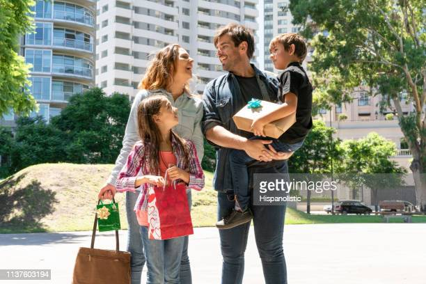 beautiful latin american family outside father carrying son while couple laughs at something - hispanolistic stock photos and pictures