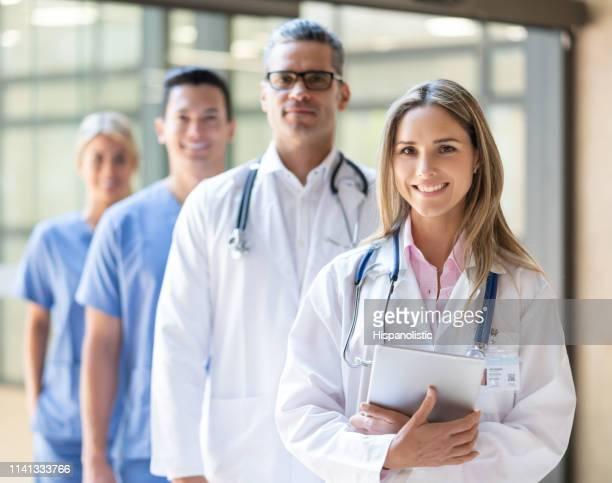 mooie latijns-amerikaanse vrouwelijke arts leidt haar team in het ziekenhuis alle glimlachen op camera - huisarts stockfoto's en -beelden