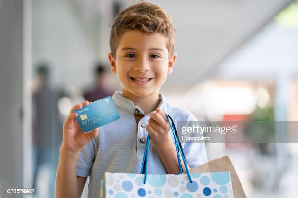 beautiful latin american little boy holding a credit card and shopping bags while looking at camera smiling - indulgence stock pictures, royalty-free photos & images